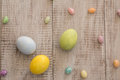 Colored Painted Easter Eggs and Jelly Beans on White Wood Backgr