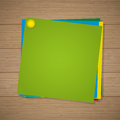 Colored paper for notes with a pin attached on the wooden background Royalty Free Stock Photo