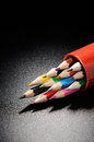 Colored pencils on a black grained surface of table Royalty Free Stock Photos