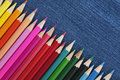 Colored pencils on a blue jeans background. Panorama. Royalty Free Stock Photo
