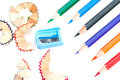 Colored pencils of different colors and a pencil sharpener shavings on white background Stock Images