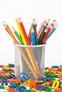 Colored pencils and letters many in a holder before white background surrounded by colorful wooden Royalty Free Stock Images