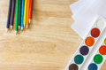 Colored pencils, lying like rainbow, paper and watercolor on wooden background Royalty Free Stock Photo