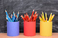 Colored pencils in matching pencil cups closeup of front of a school room chalkboard the are covered red blue and Stock Images