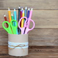 Colored pencils and scissors in a decorative tin can. Recycled tin can for storage of stationery isolated on wooden background Royalty Free Stock Photo