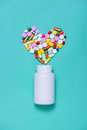 Colored pills in heart shape with bottle  on blue background. Royalty Free Stock Photo