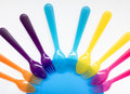 Colored plastic forks and spoons , on a plate, the background on Royalty Free Stock Photo