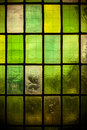 Colored stained glass window with regular block pattern green tone multicolored in hue of Stock Image