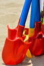 Colored toy shovel on sand as beautiful color and shape and holiday for children Stock Photo