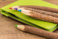 Colored wooden pencils and green brown leather workbook on a table Stock Photos