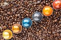 Capsules of Coffee placed on a bed of coffee beans Royalty Free Stock Photo