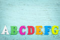 Colorful alphabet letters with copy space on light blue wooden background Royalty Free Stock Photography