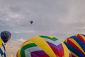 Colorful array of hot air balloons float through the sky at dusk as others prepare to launch
