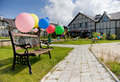 Colorful balloons near brench on alley and houses Royalty Free Stock Photography