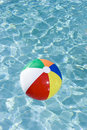 Colorful beach ball floating in swimming pool Royalty Free Stock Photo