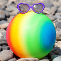 Colorful beach ball with sunglasses on the pebbles summer holidays concept rainbow Stock Photos