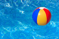 A colorful beach ball floating in a swimming pool