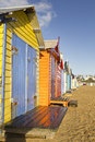 Colorful beach bright brighton bathing boxes with a blue sky Stock Photos