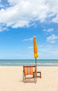 Colorful beach chair and closed umbrella on beautiful beach with cloudy blue sky concept for rest relaxation holiday in Royalty Free Stock Image