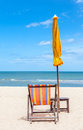 Colorful beach chair and closed umbrella on beautiful beach with cloudy blue sky concept for rest relaxation holiday in Royalty Free Stock Photo