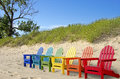 Colorful beach chairs row of in sand with sand dune background Royalty Free Stock Images