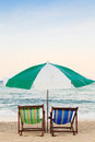 Colorful beach chairs and umbrella on the beach before sunset Stock Photos