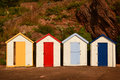 Colorful beach huts at goodrington devon in england yellow red light blue blue doors Stock Images