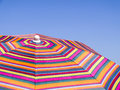 Colorful beach umbrella against the blue sky. Striped texture Royalty Free Stock Photo