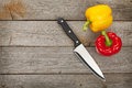 Colorful bell peppers and kitchen knife over wooden table background with copy space Stock Photography