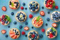 Colorful berry tartlets or cake for kitchen pattern. Pastry dessert from above. Royalty Free Stock Photo