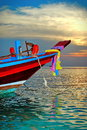 Colorful boat at sunset in crystal clear blue turquoise water Royalty Free Stock Photo