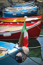 Colorful boats and italian flag float in turquoise water in the cinque terre region of italy Stock Photography