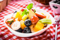 Colorful bowl of tropical fruit salad with blueberries kiwifruit orange apple banana grapes and orange for a healthy summer picnic Stock Photography