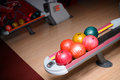 Colorful bowling balls sitting in the ball return Royalty Free Stock Photo
