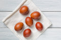 Colorful brown easter eggs on cloth and white wooden table Royalty Free Stock Photo