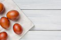 Colorful brown easter eggs on cloth and white wooden table with free space. Focus on eggs Royalty Free Stock Photo