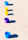Colorful buckets on the beach sand row of Stock Image
