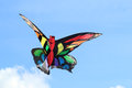 Colorful butterfly kite against a blue sky flying in the background Stock Photos