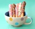 Colorful cake pops stick in polka dot cup.