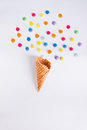 Colorful candies bang from ice cream cone on the white background. Place for lettering. Top view, flat lay.