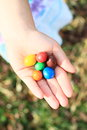 Colorful candies in hand holded on palm of kids Stock Image