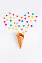 Colorful candies in the shape of a heart and ice cream cone on the white background. Place for lettering. Top view, flat lay