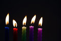 Colorful candles on black background. Blue red green violet pink candle with real flame. Soft focus, shallow depth of