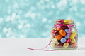 Colorful candy jar decorated with a bow against blue bokeh background Royalty Free Stock Photo