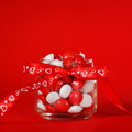 Colorful candy jar decorated with a red bow with hearts on red background. Valentines day concept Royalty Free Stock Photo