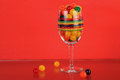 Colorful candy still life with multi colored fruit sours in and around stemmed glass against red background and reflection in Stock Images