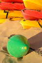 Colorful canoes and a buoy resting on sunny beach sand Stock Photos