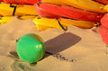 Colorful canoes and a buoy resting on sunny beach sand Royalty Free Stock Photography