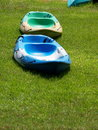 Colorful canoes on a lake bank with nice green grass for rent in city park in bangkok Royalty Free Stock Photography