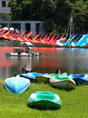 Colorful canoes on a lake bank with nice green grass for rent in city park in bangkok with art installation in the Royalty Free Stock Photography